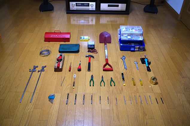 リビングの真ん中にハンマーやスコップなど、たくさんの工具を並べた写真