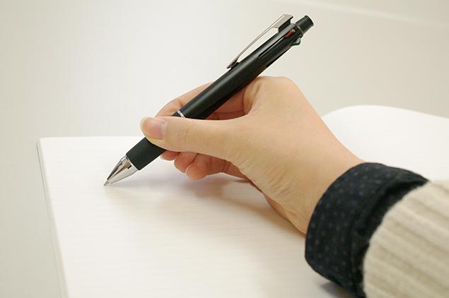 紙のノートに、ボールペンで書いているところの写真