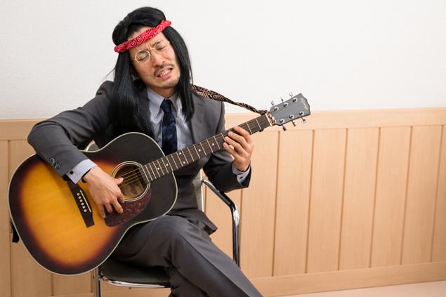 スーツでギターを弾いているトン太の写真