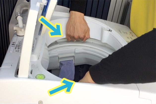 洗濯機の内側に手を入れている写真