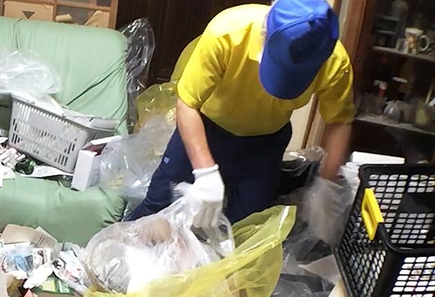 ゴミを指定袋に入れている写真