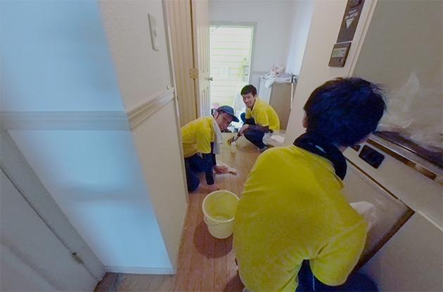 汚部屋の玄関を掃除している写真