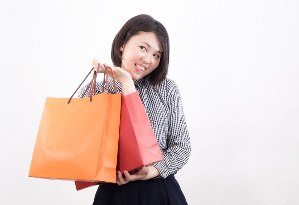 バーゲンで買い物をして喜ぶ女性の写真