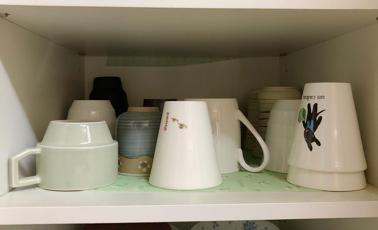 乱雑にコップ類が入っている食器棚の写真
