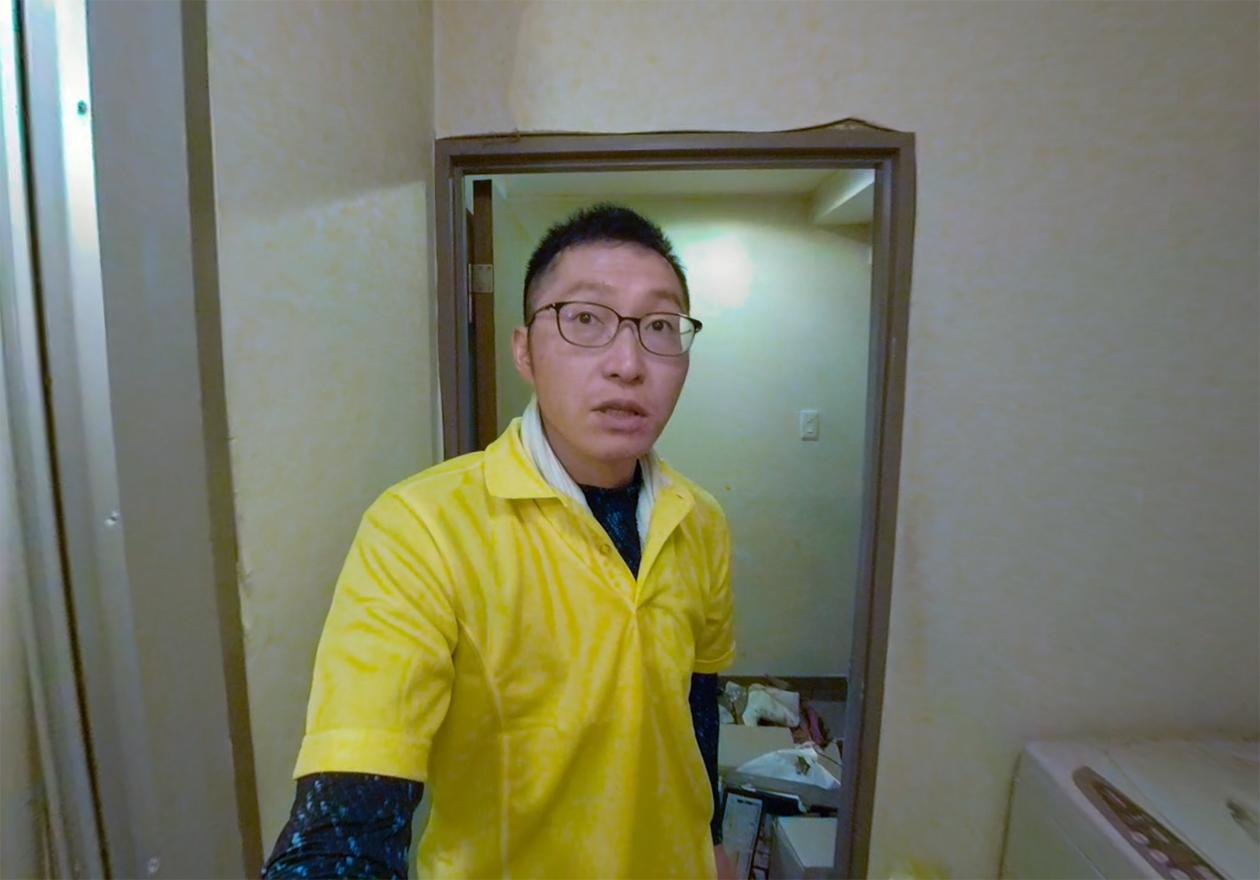 スタッフの岡本が洗濯機の前に立っている写真