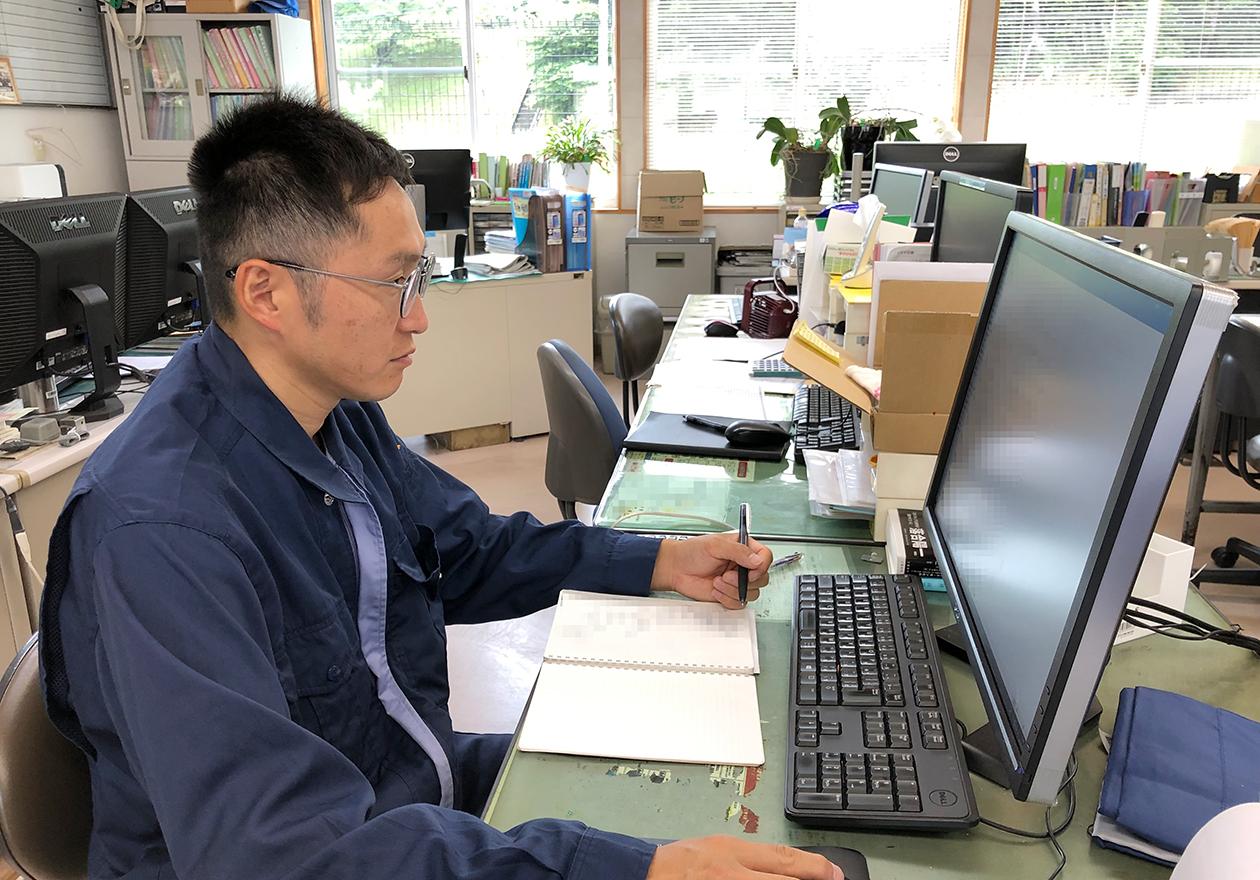 スタッフの岡本がメールをチェックしている写真