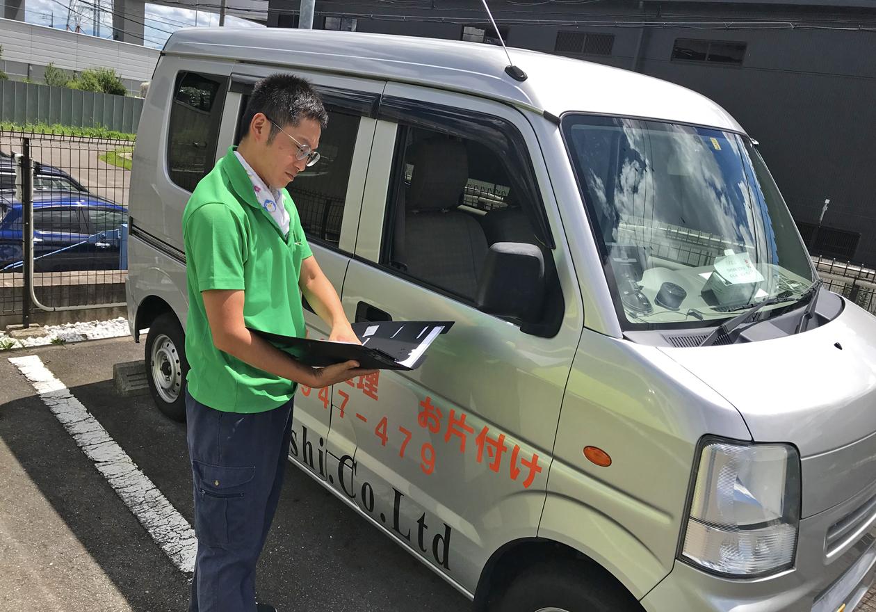 車の前で立つ岡本さんの写真