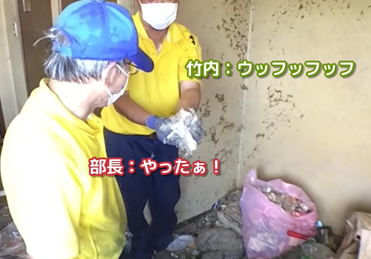 舞い散る羽毛と釣り道具の汚部屋!作業中、羽毛布団を持つ竹内さんの画像