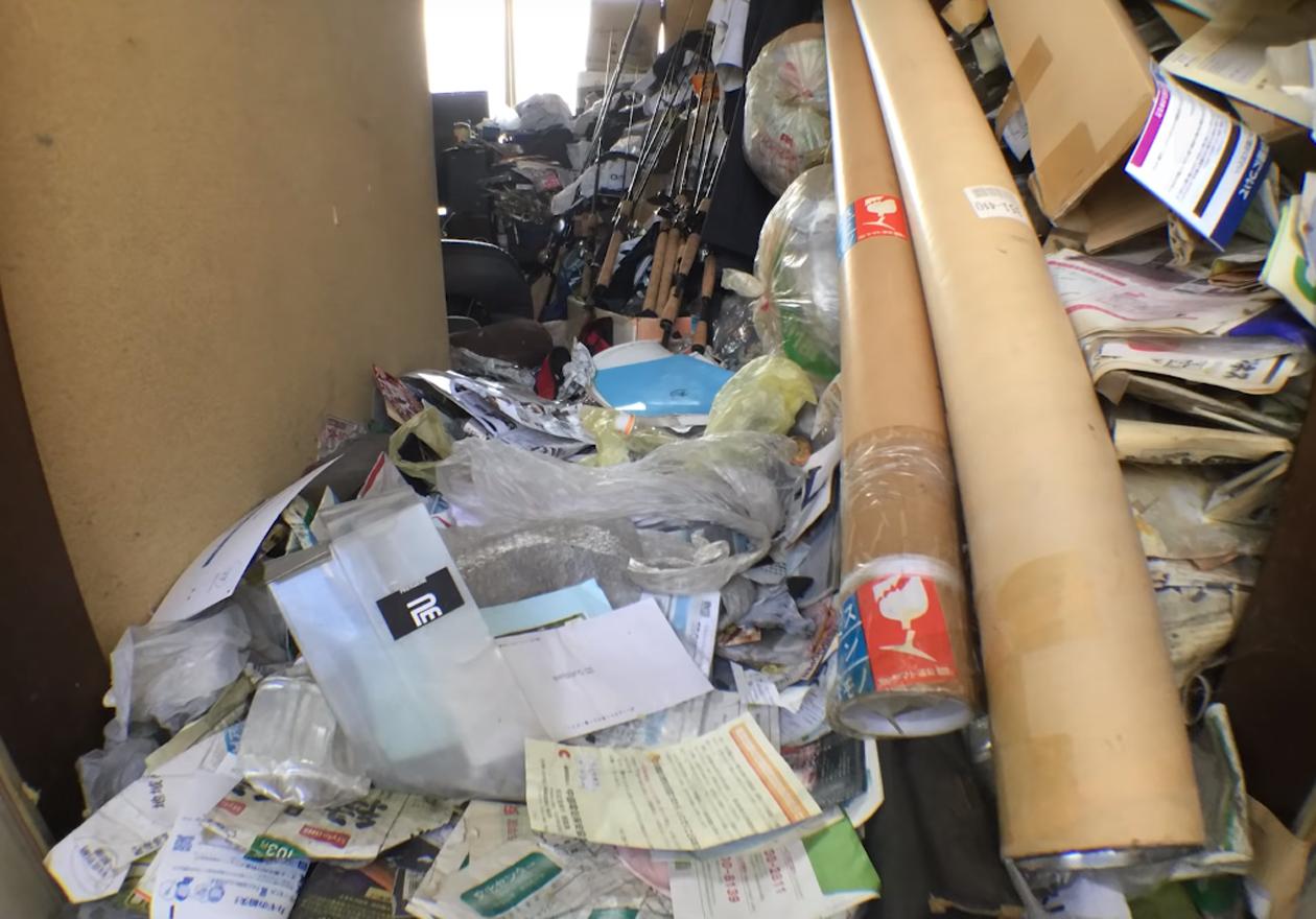 舞い散る羽毛と釣り道具の汚部屋!作業前、玄関の画像