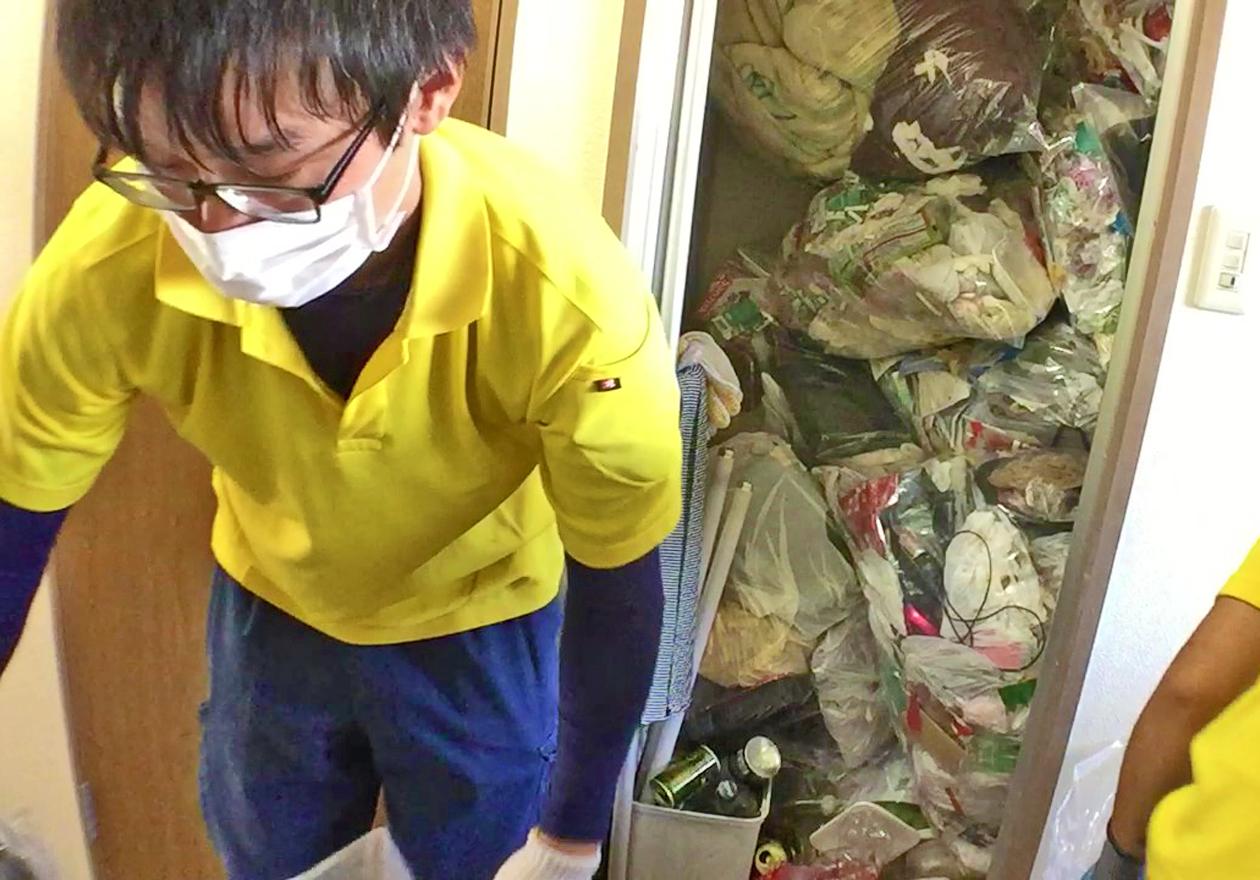 ゴミ屋敷のお風呂場にゴミを集める写真