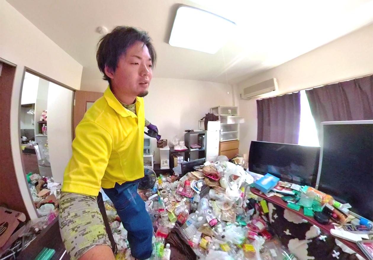 ゴミ屋敷のリビングを撮影する古畑さんの写真