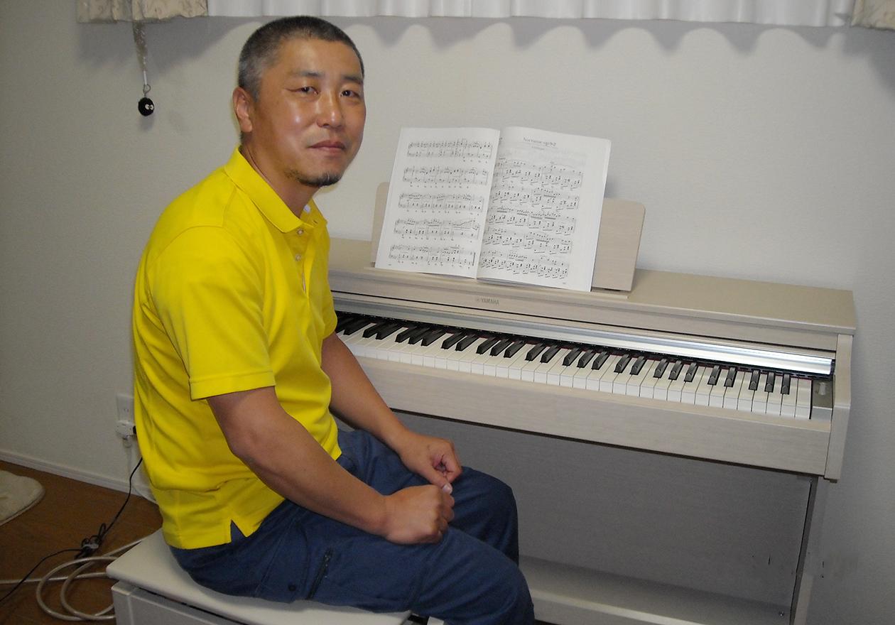 竹内がピアノの前に座っている写真