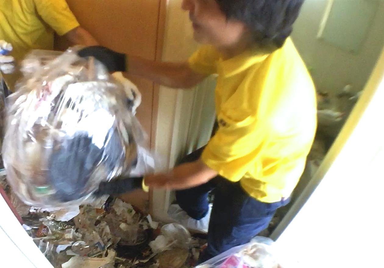 袋詰めしたゴミをスタッフへ手渡している様子
