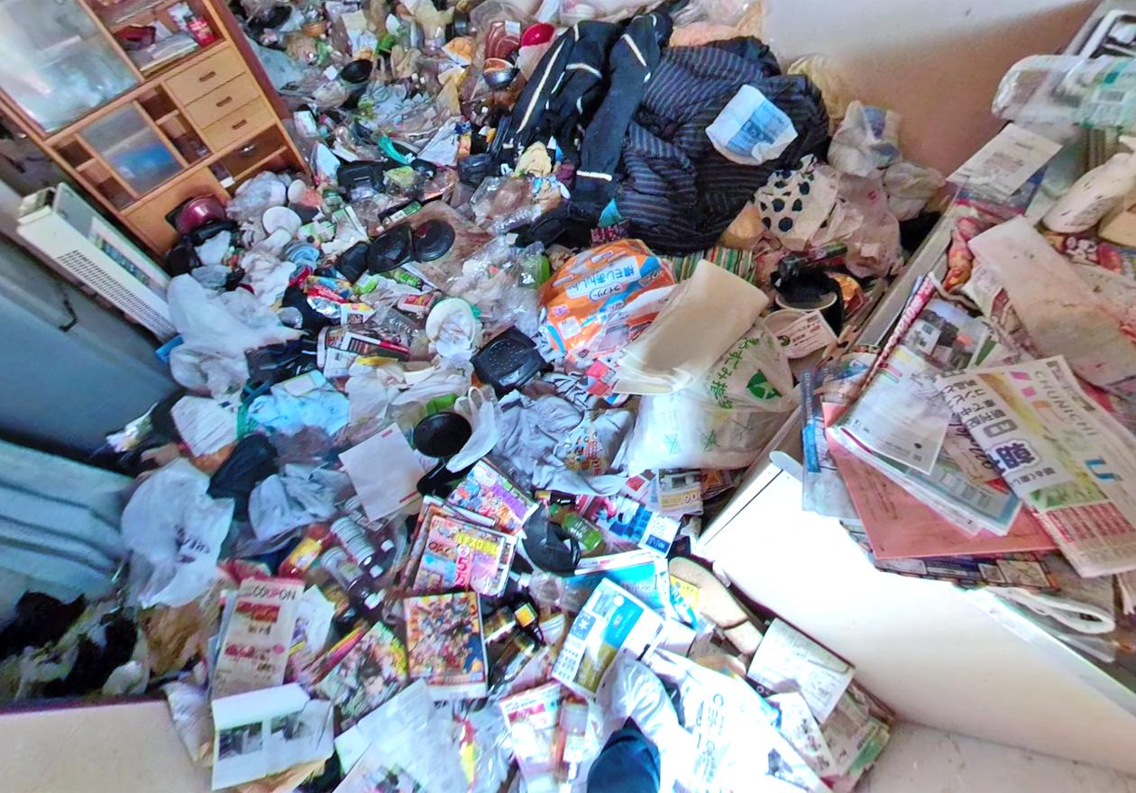 パターン3.弁当の空き容器、ペットボトル、雑誌、衣類など、さまざまな物が混在しているゴミ屋敷の写真