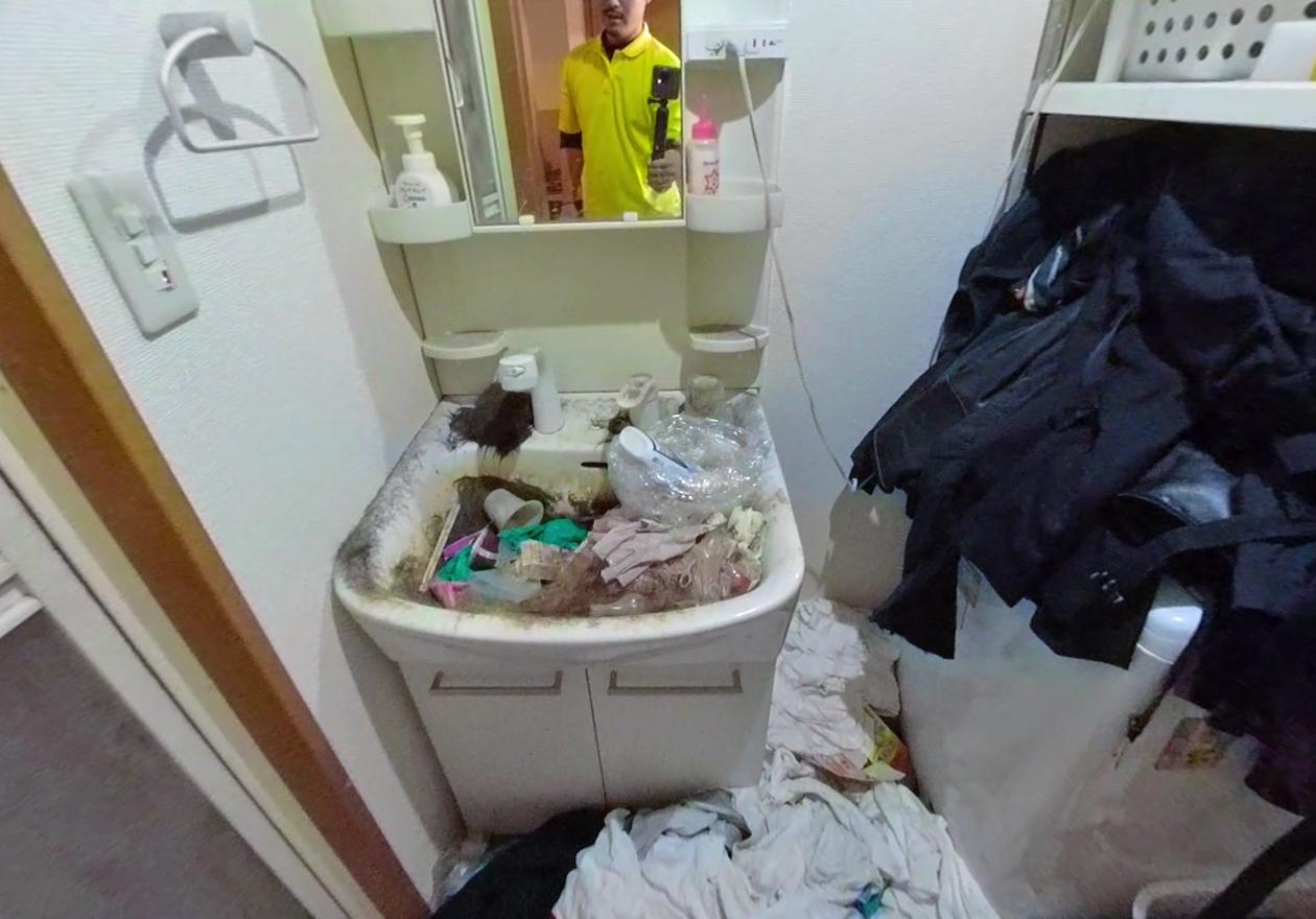 床に服が散らばっており、洗面台に髪の毛がたくさんある様子