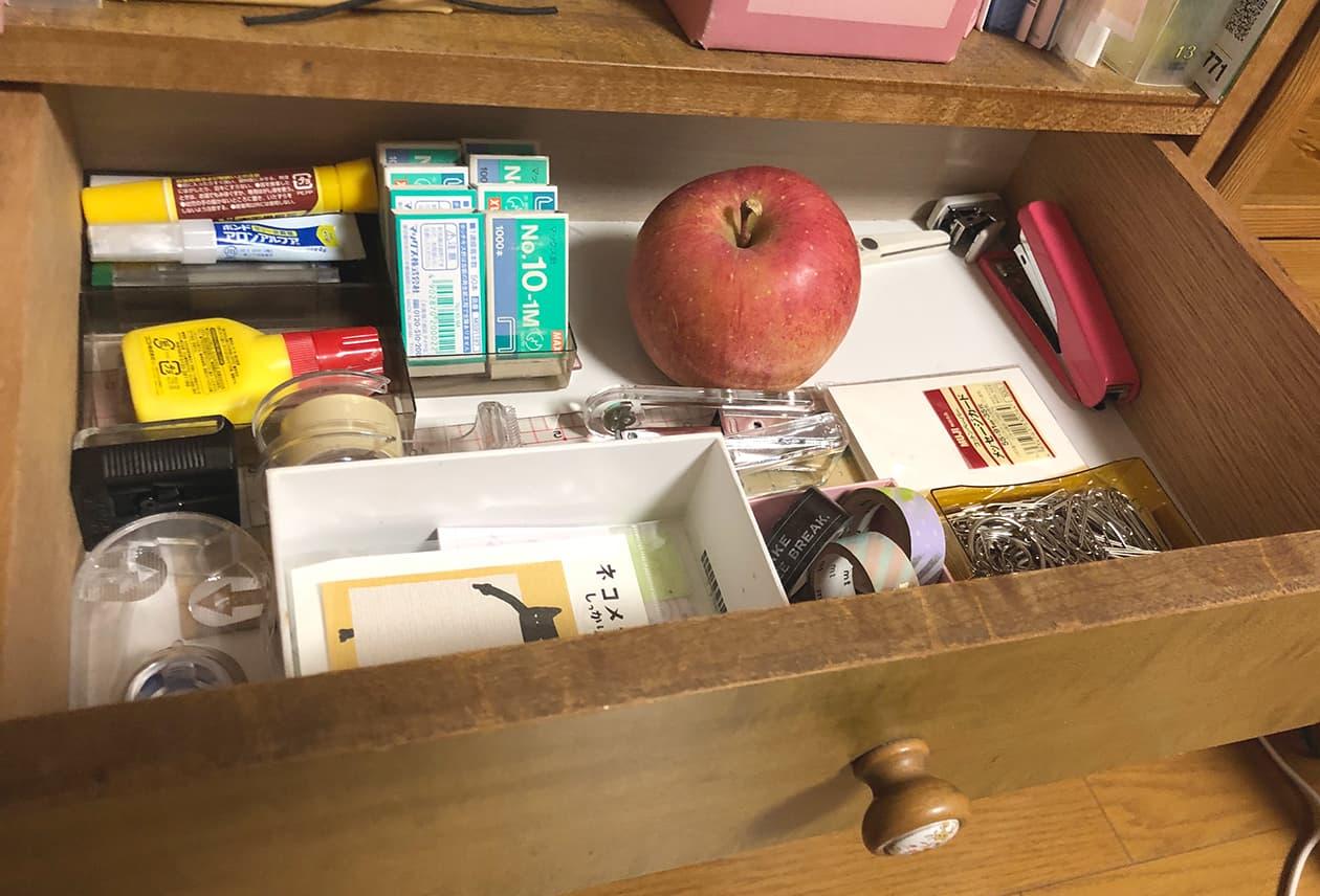 リンゴと文房具が同じ引き出しに入っている写真
