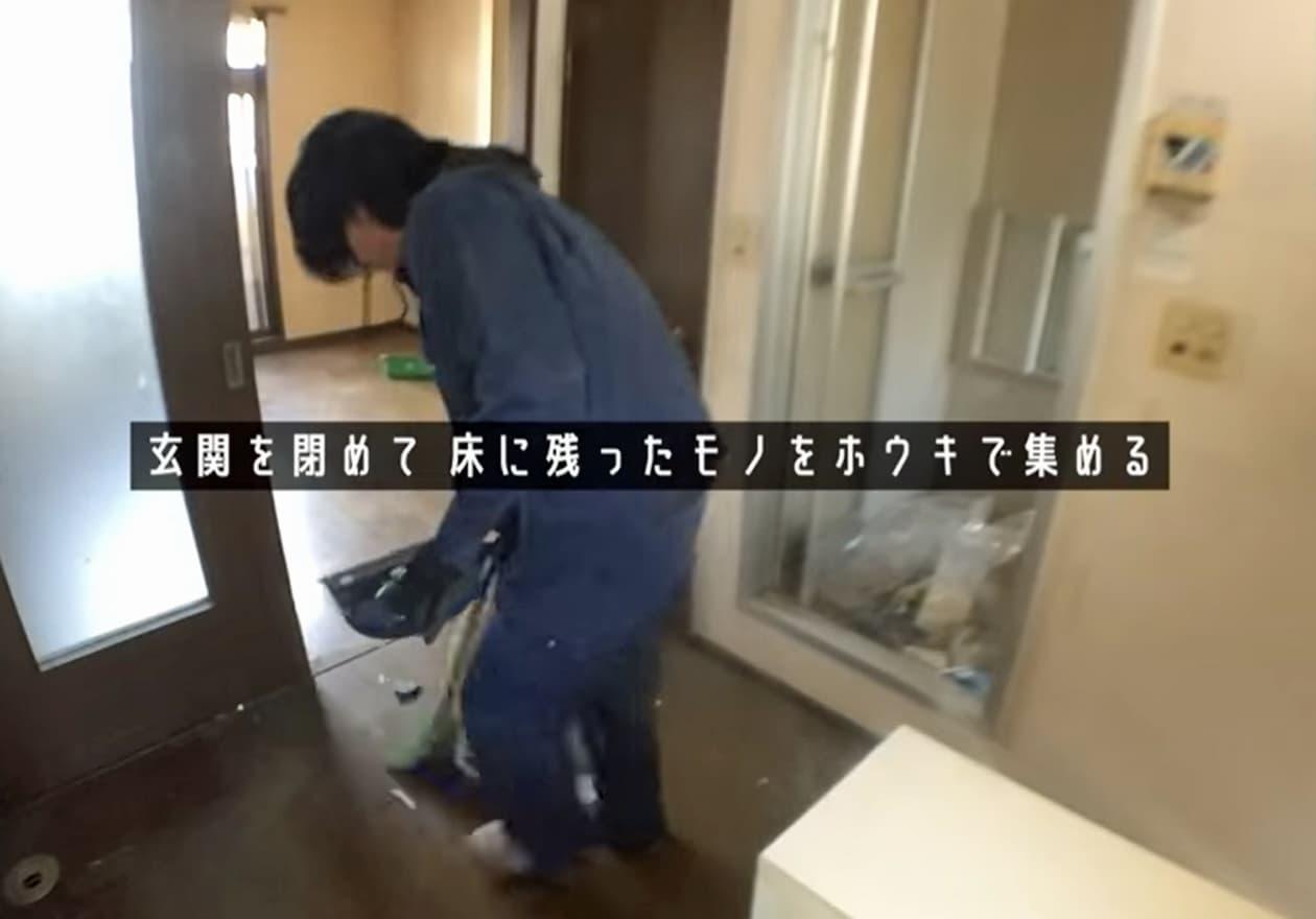 玄関周辺の掃き掃除をしている安永の様子
