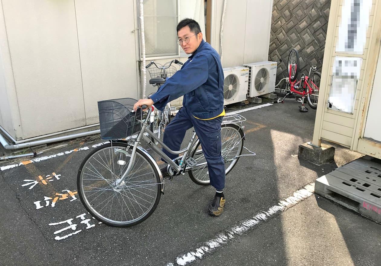 自転車で見積もりに向かう岡本さんの様子