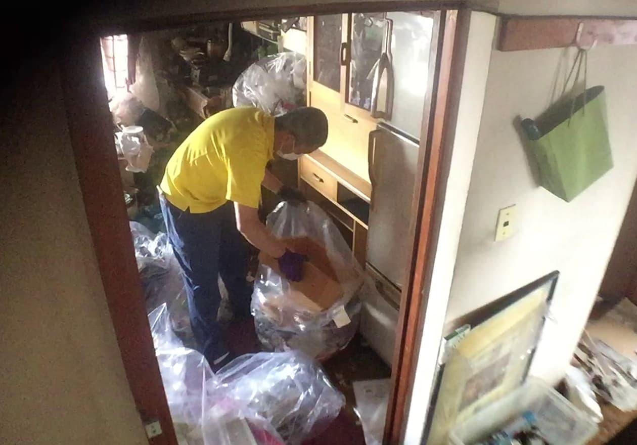 キッチンにある食器棚の引き出しを袋詰めしている竹内の様子