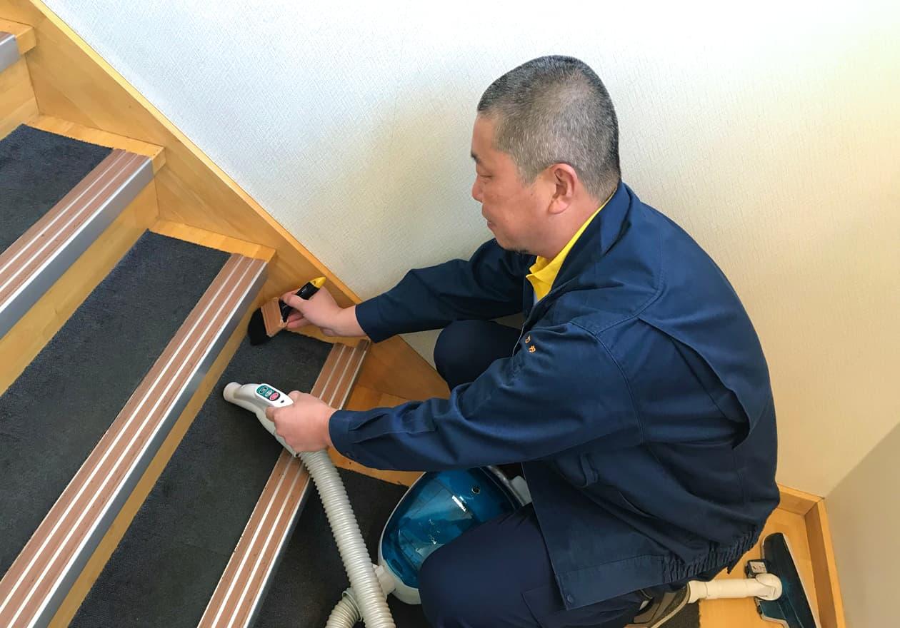 刷毛(はけ)と掃除機で階段を掃除している竹内の様子