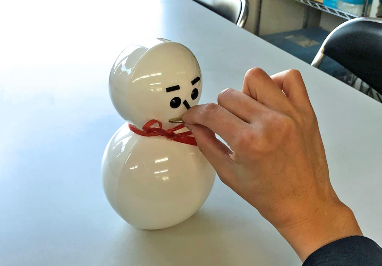 雪だるま弁当箱の口に500円玉を入れる様子の写真