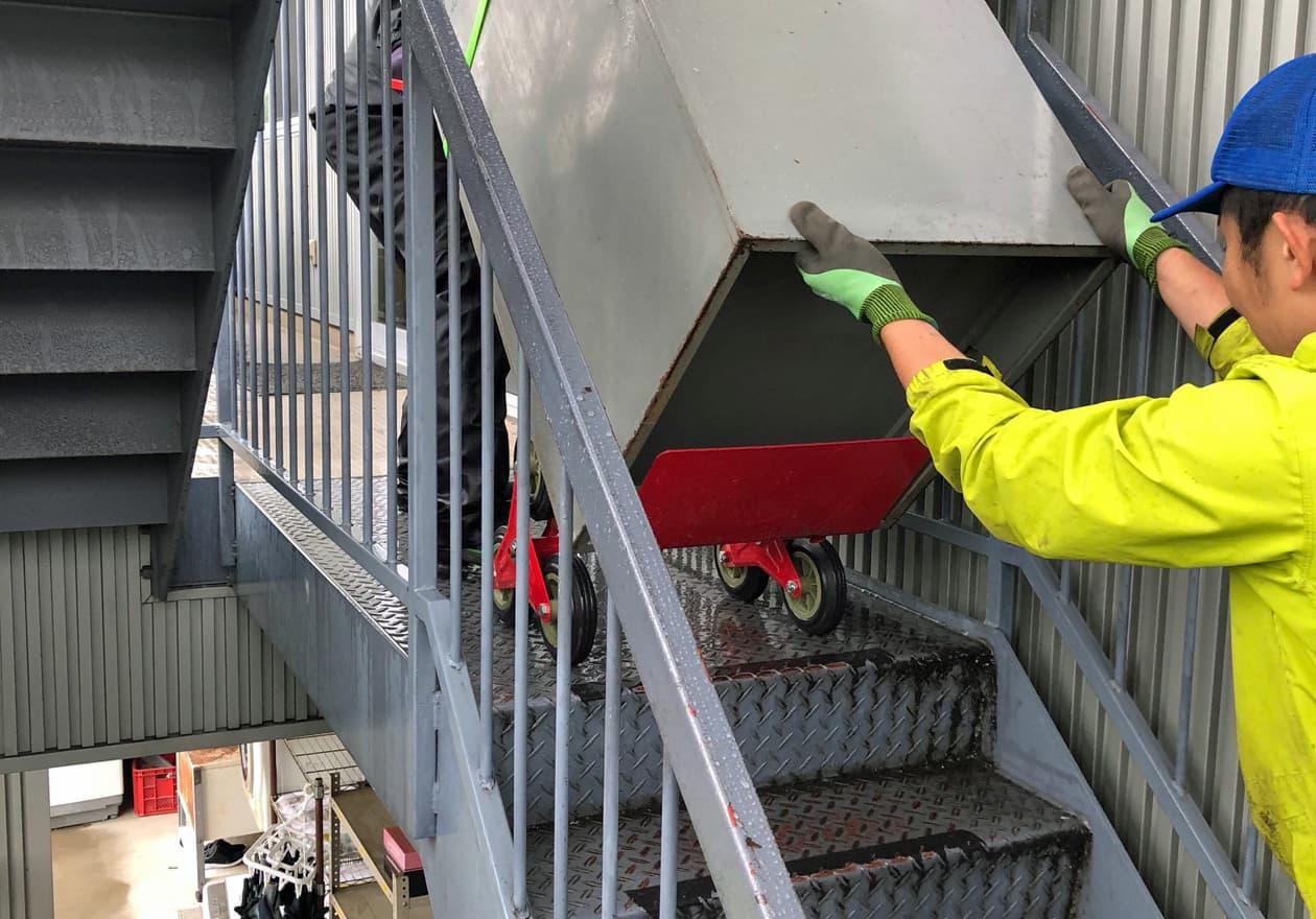 階段で三輪階段昇降機を使って荷物を降ろしている様子