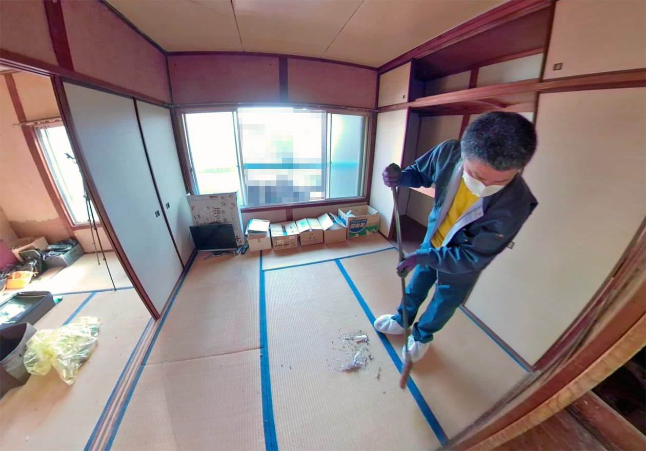 和室の掃き掃除をしている竹内の様子