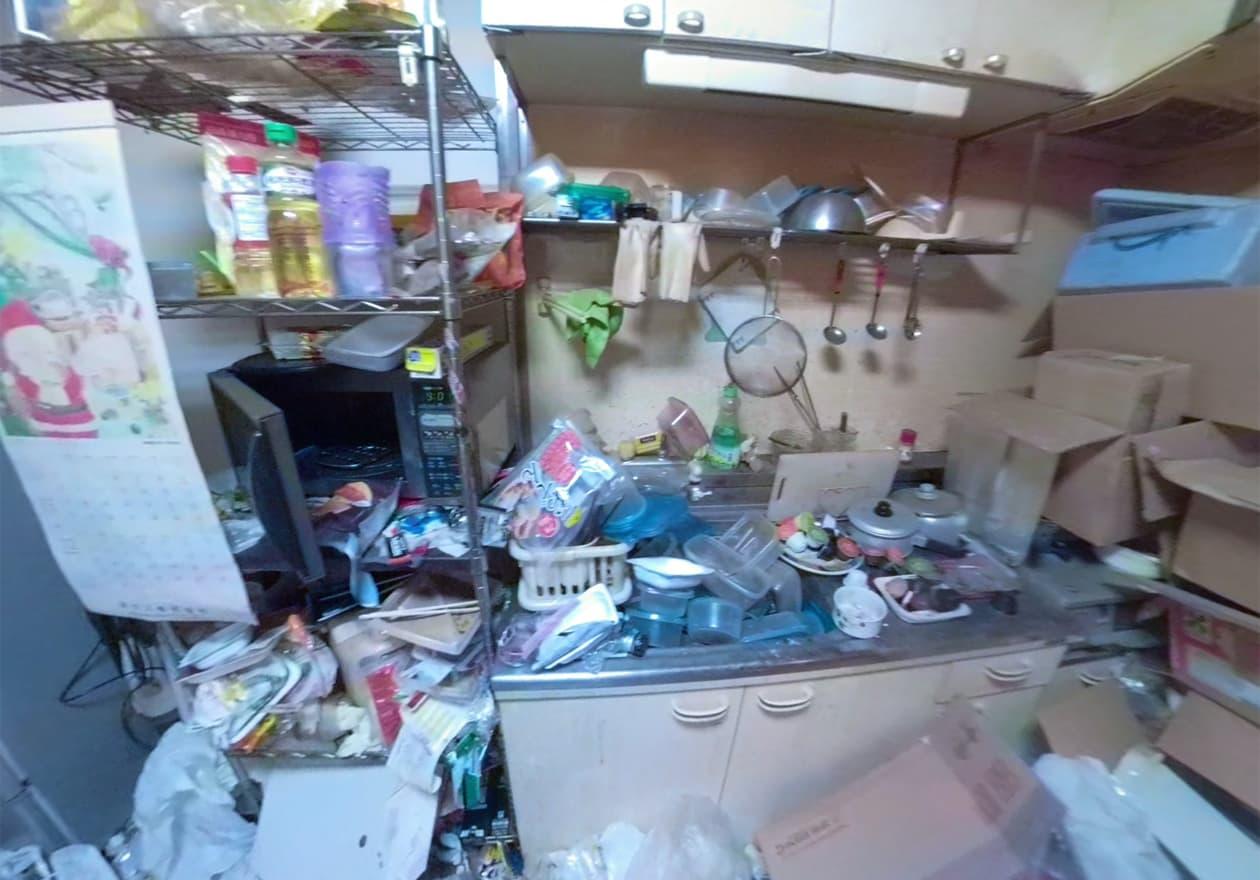 シンクにはタッパーなどの洗い物、ガスコンロ周辺にはダンボールが積み重なっているキッチン周辺の様子