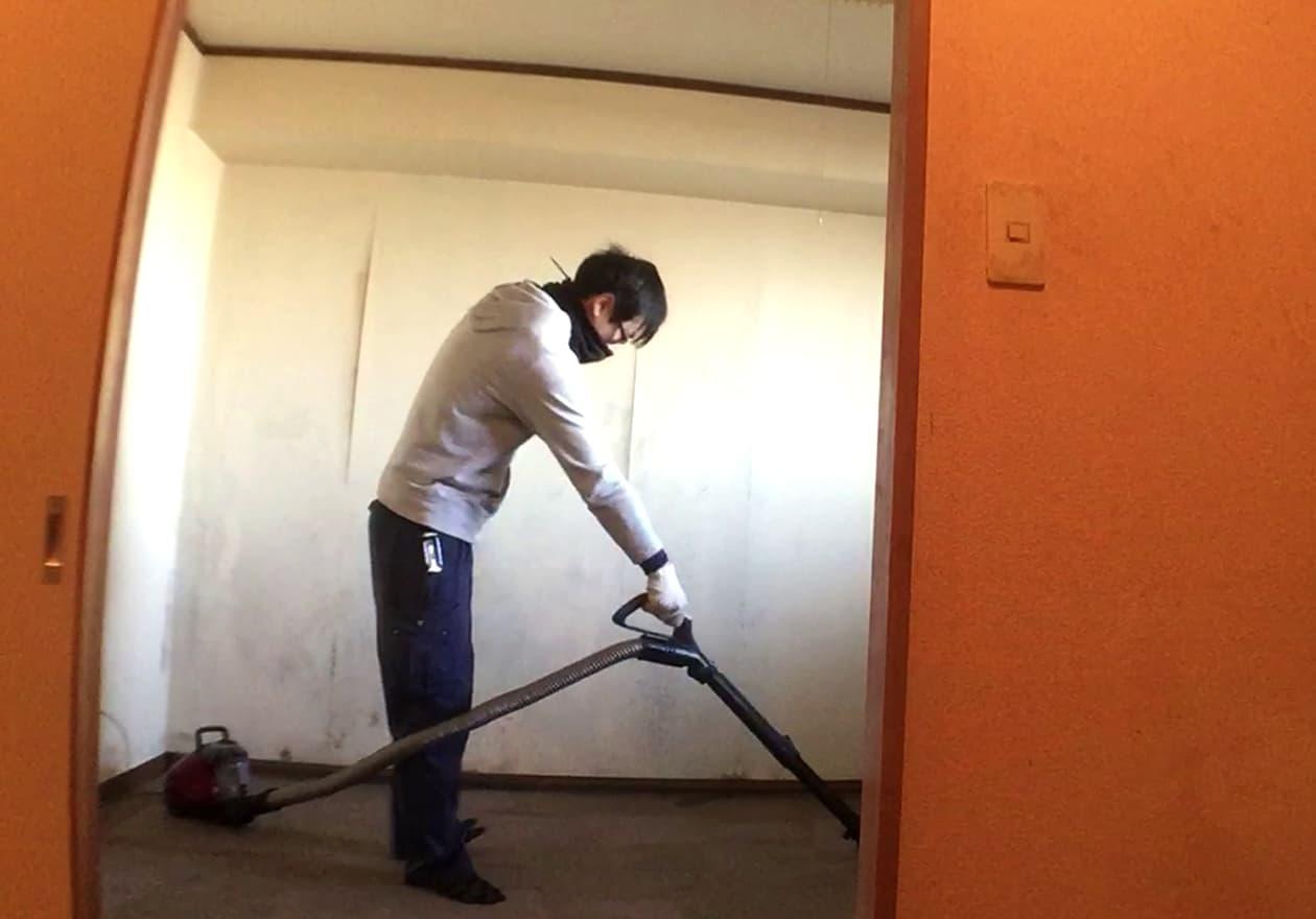 北側の部屋を掃除機掛けしている竹内の様子
