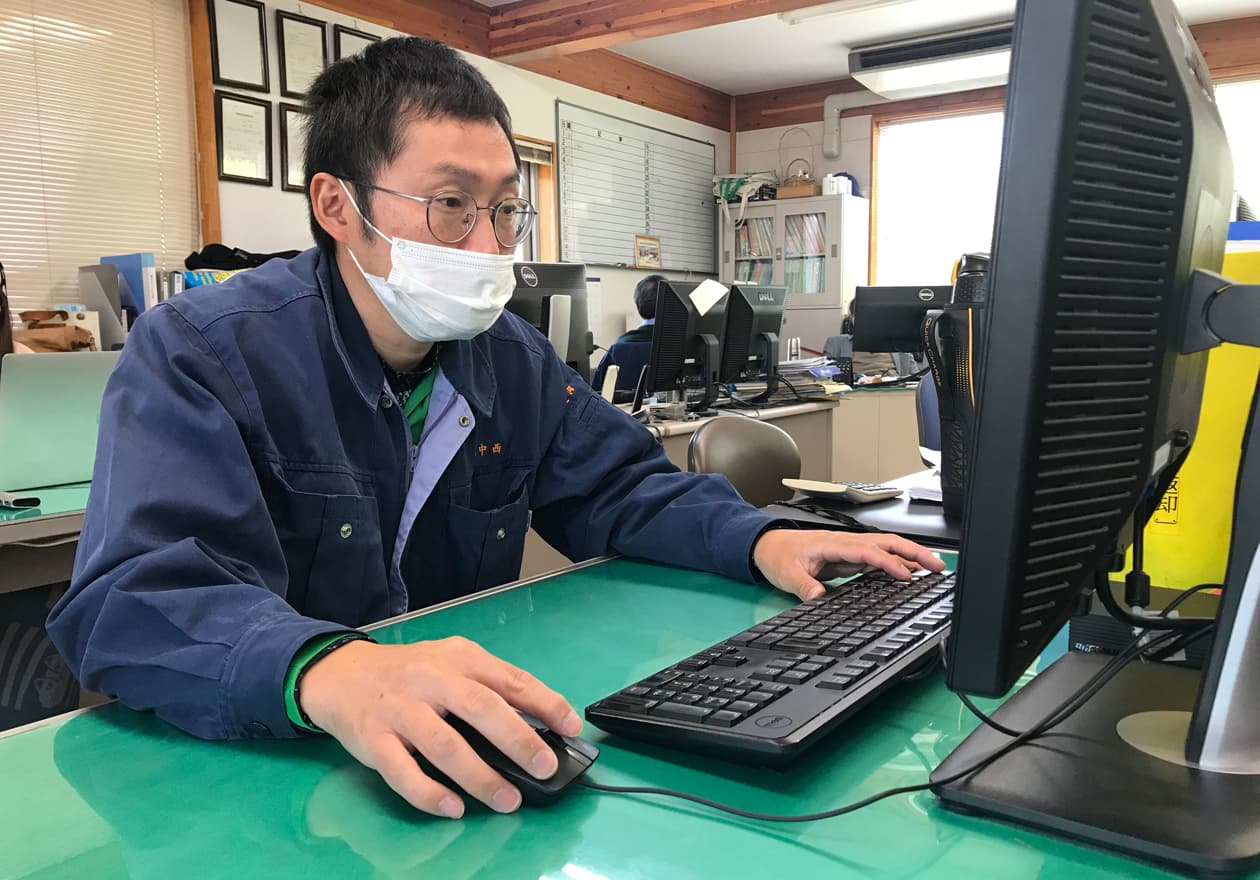 パソコンでメールを確認している岡本の様子