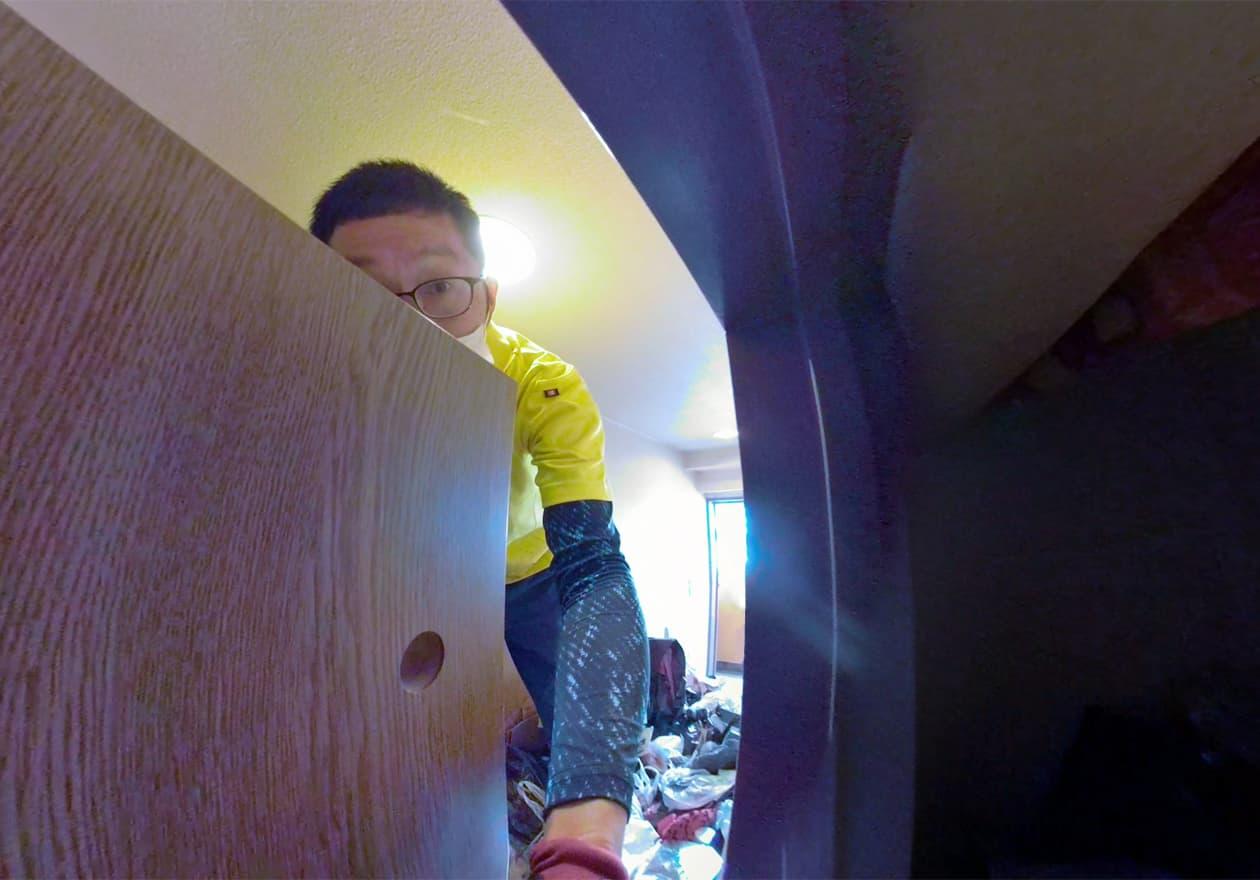 トイレの隙間から手を入れて中の様子を撮影している岡本の様子