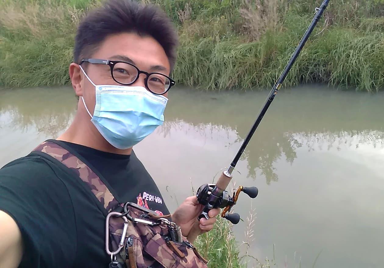 土手で釣りをしている高橋さんの様子