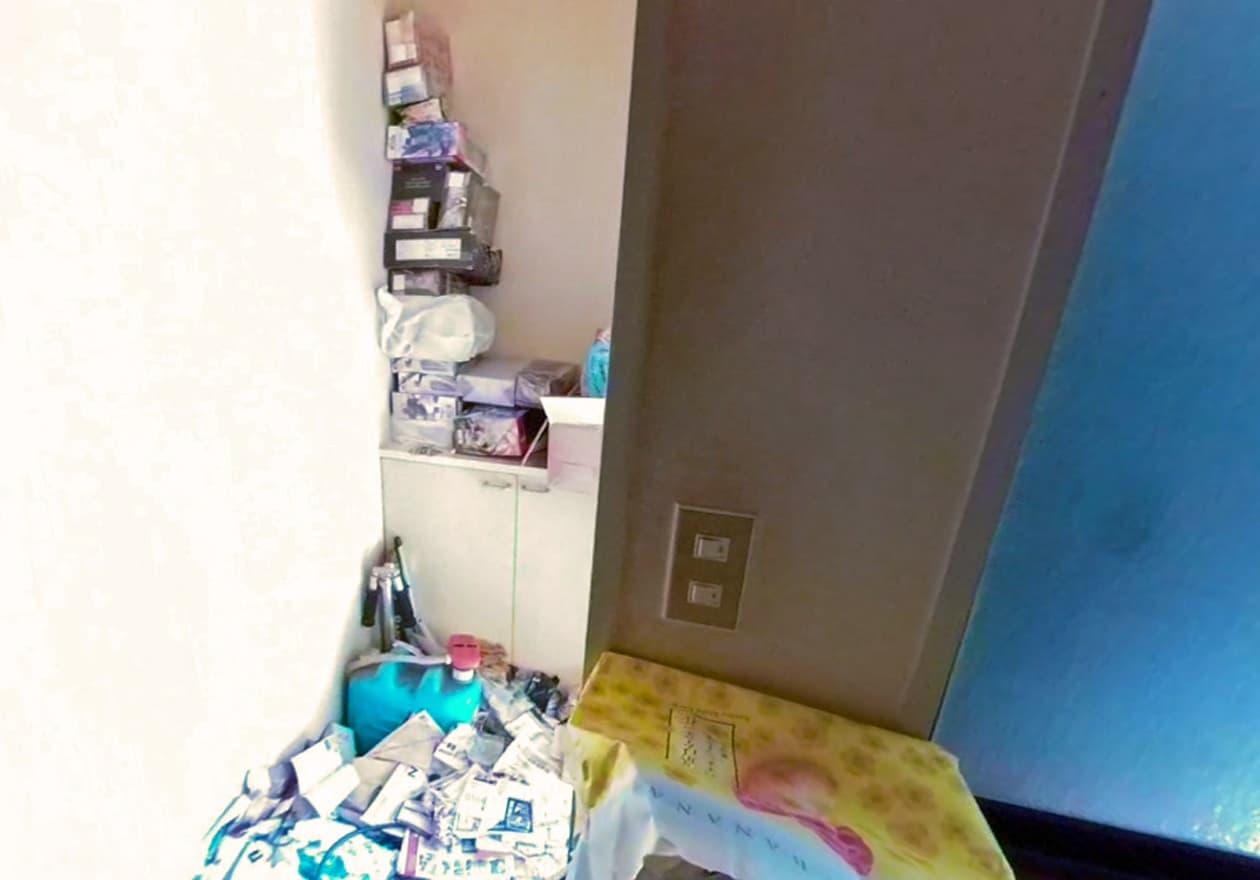 片付け中の玄関、下駄箱の上にたくさんのグッズが積み重なっている様子