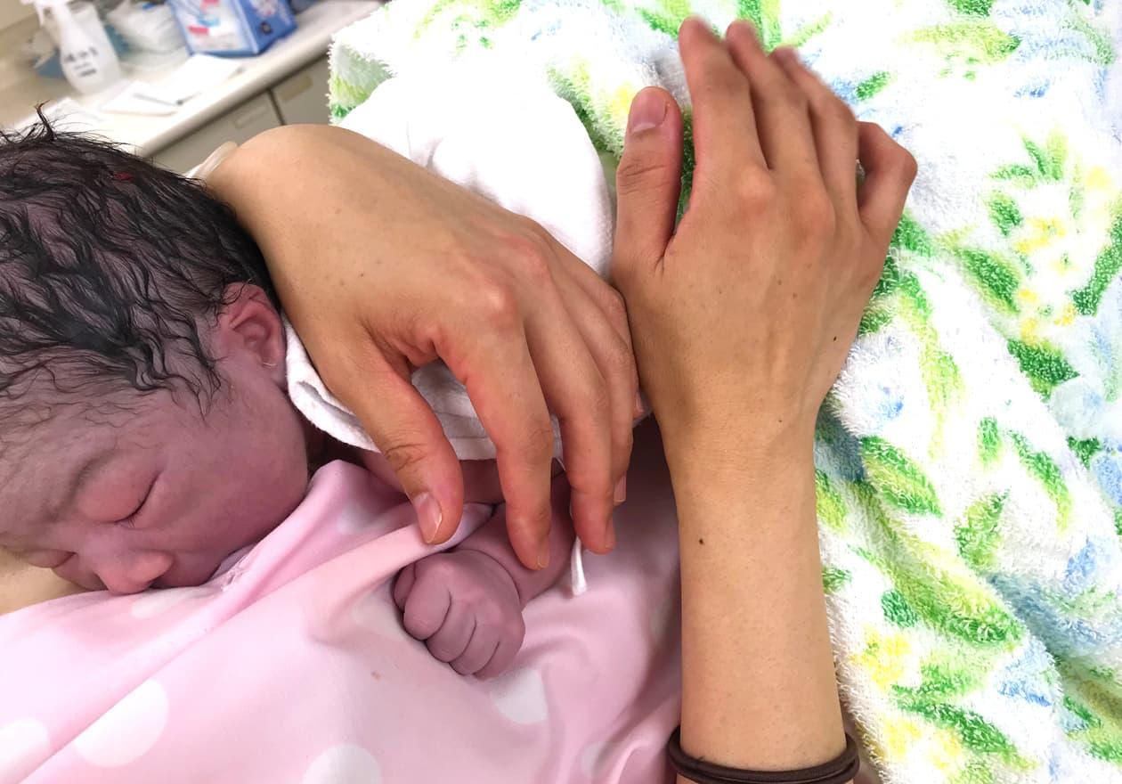 カンガルーケア中の生まれたばかりの赤ちゃんの写真