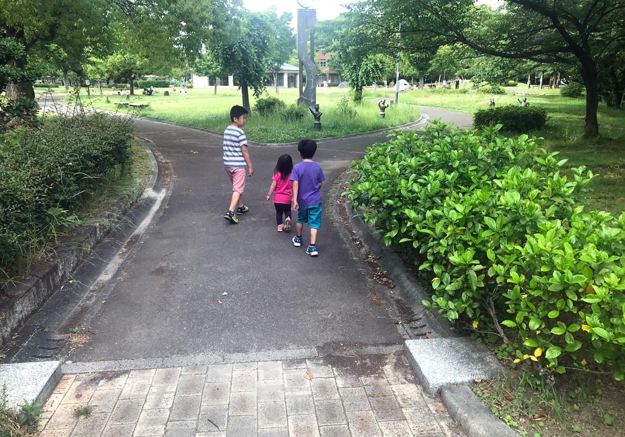公園の中へと進んで行く3人の子どもたち