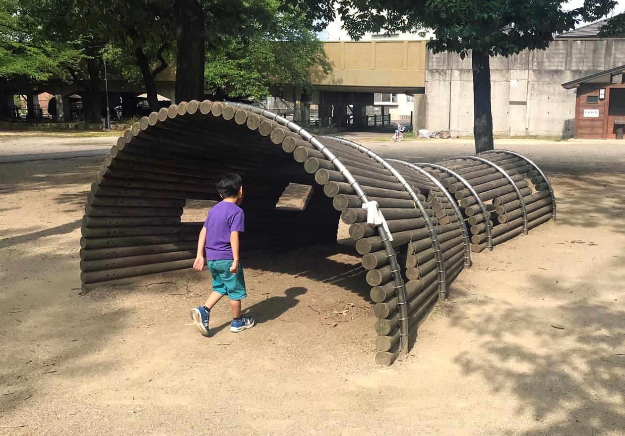 ガリバートンネルのような遊具をくぐろうとしている子どもの写真