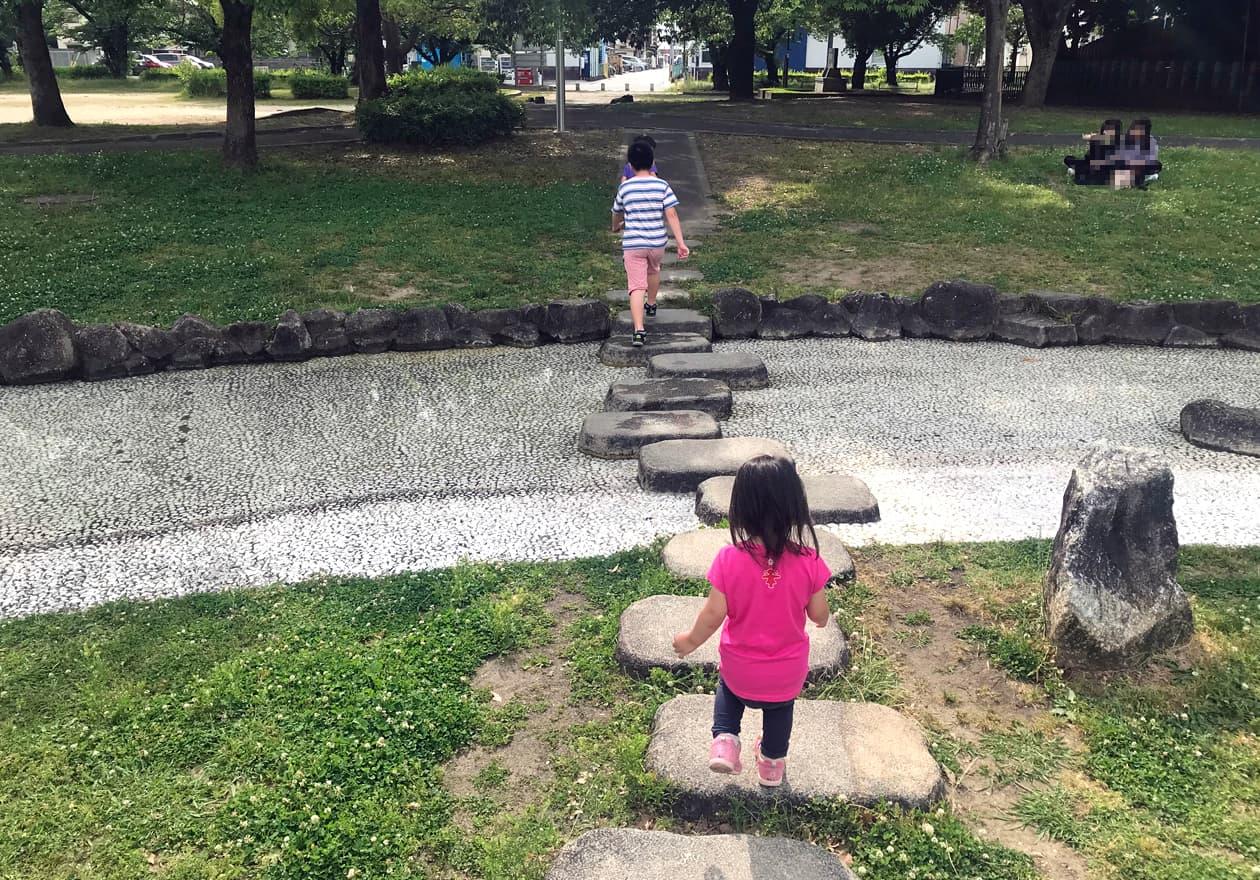 飛び石を渡る3人の子どもたち