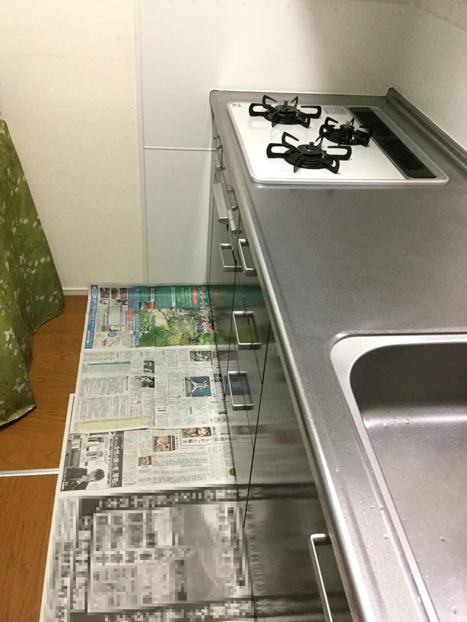 キッチンの床一面に新聞を敷いた様子
