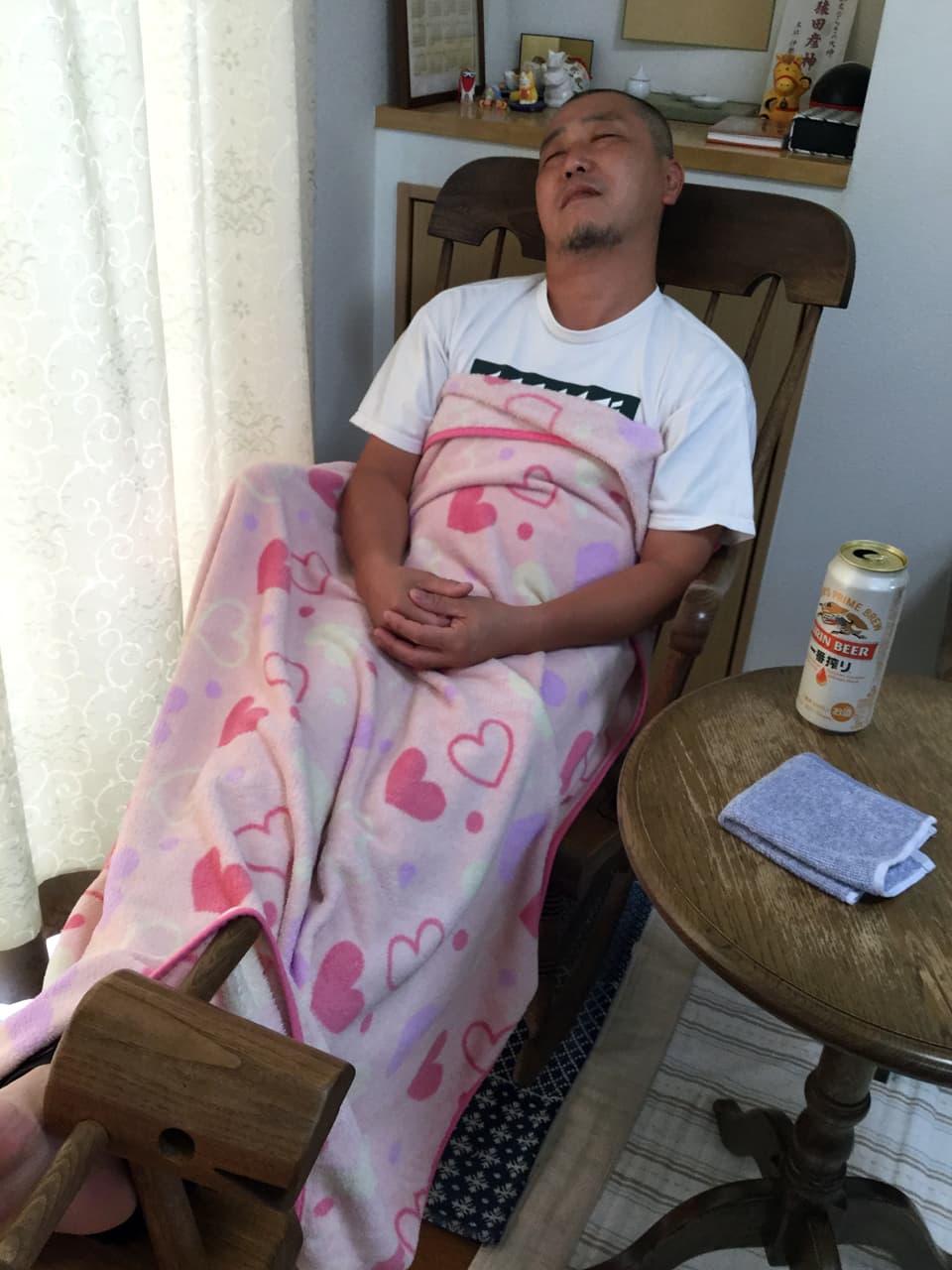 椅子の上でピンクのタオルケットをかけて寝ている竹内の様子