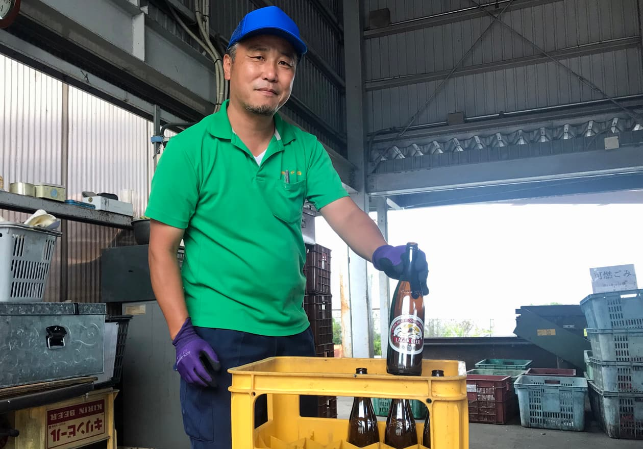 ビールビンを専用ケースに笑顔で入れている竹内の様子