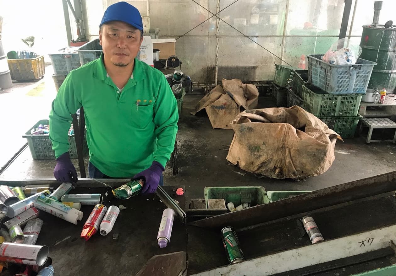 穴あけの機械にスプレー缶をセッティングをする竹内の様子