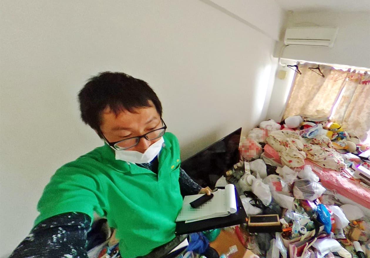 片付け前のお部屋を撮影している岡本さんの様子