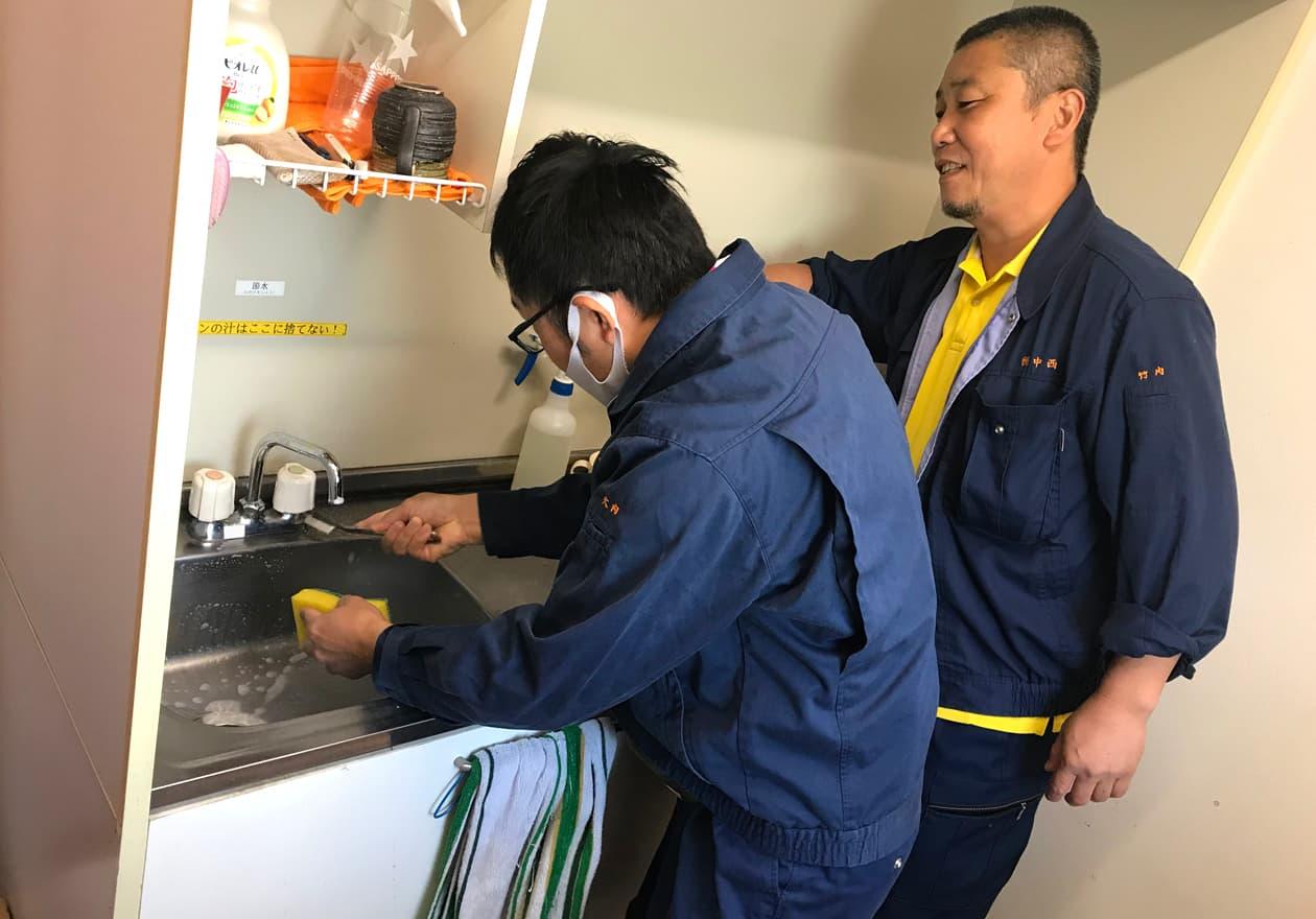 シンクを掃除している岡本に指導している竹内の様子