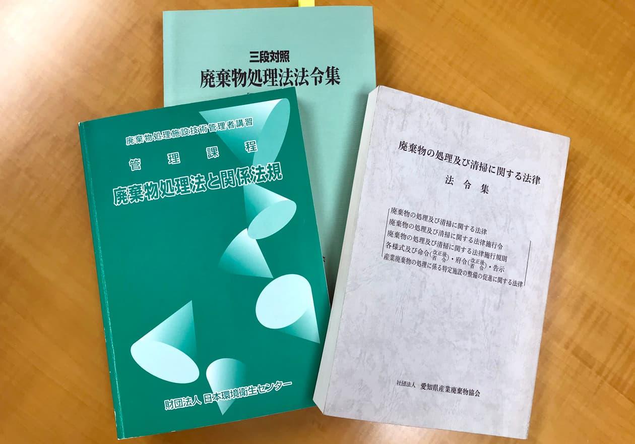 廃棄物処理法の教本を持つ竹内の様子