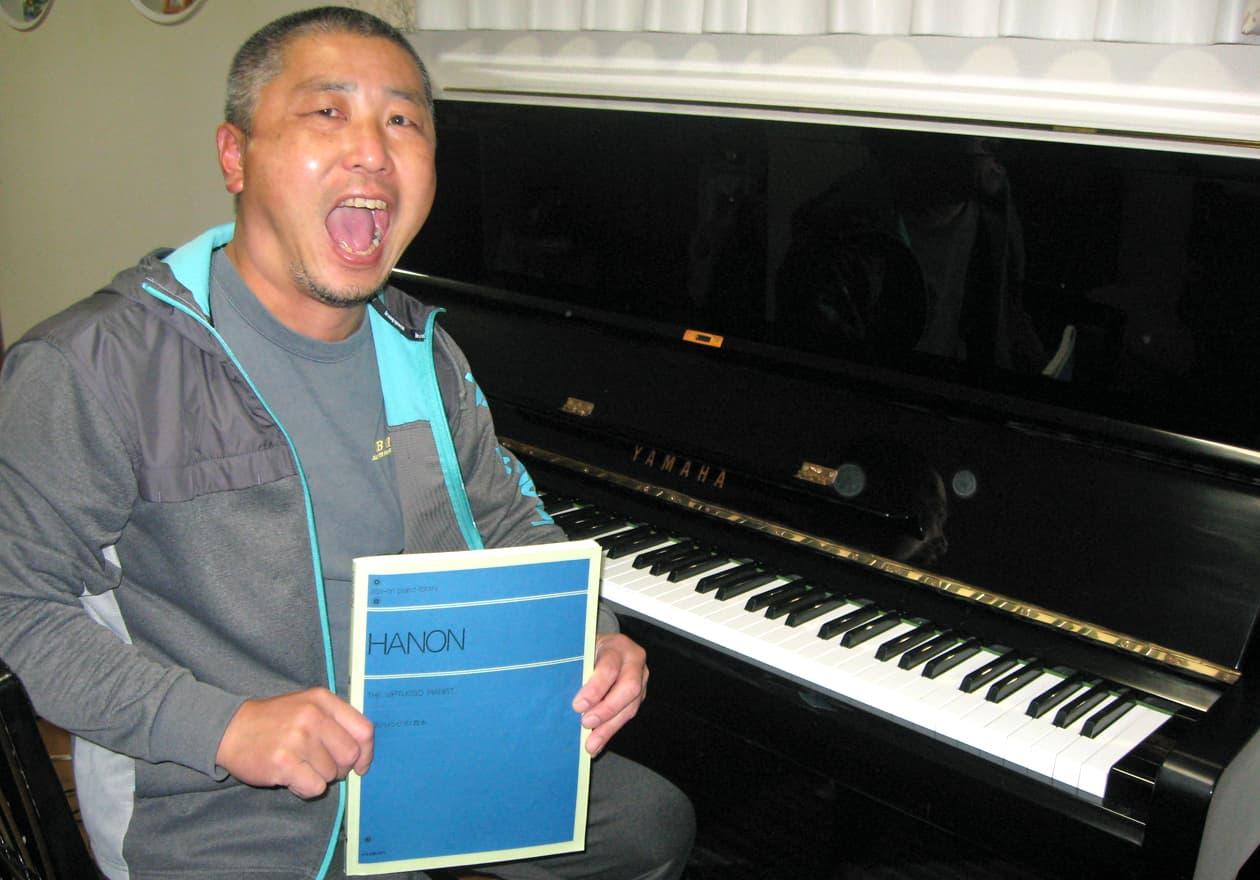 ピアノの前でHANONを持った竹内の写真