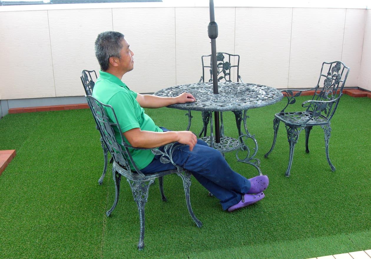 仕上がった屋上で椅子に座っている竹内の様子