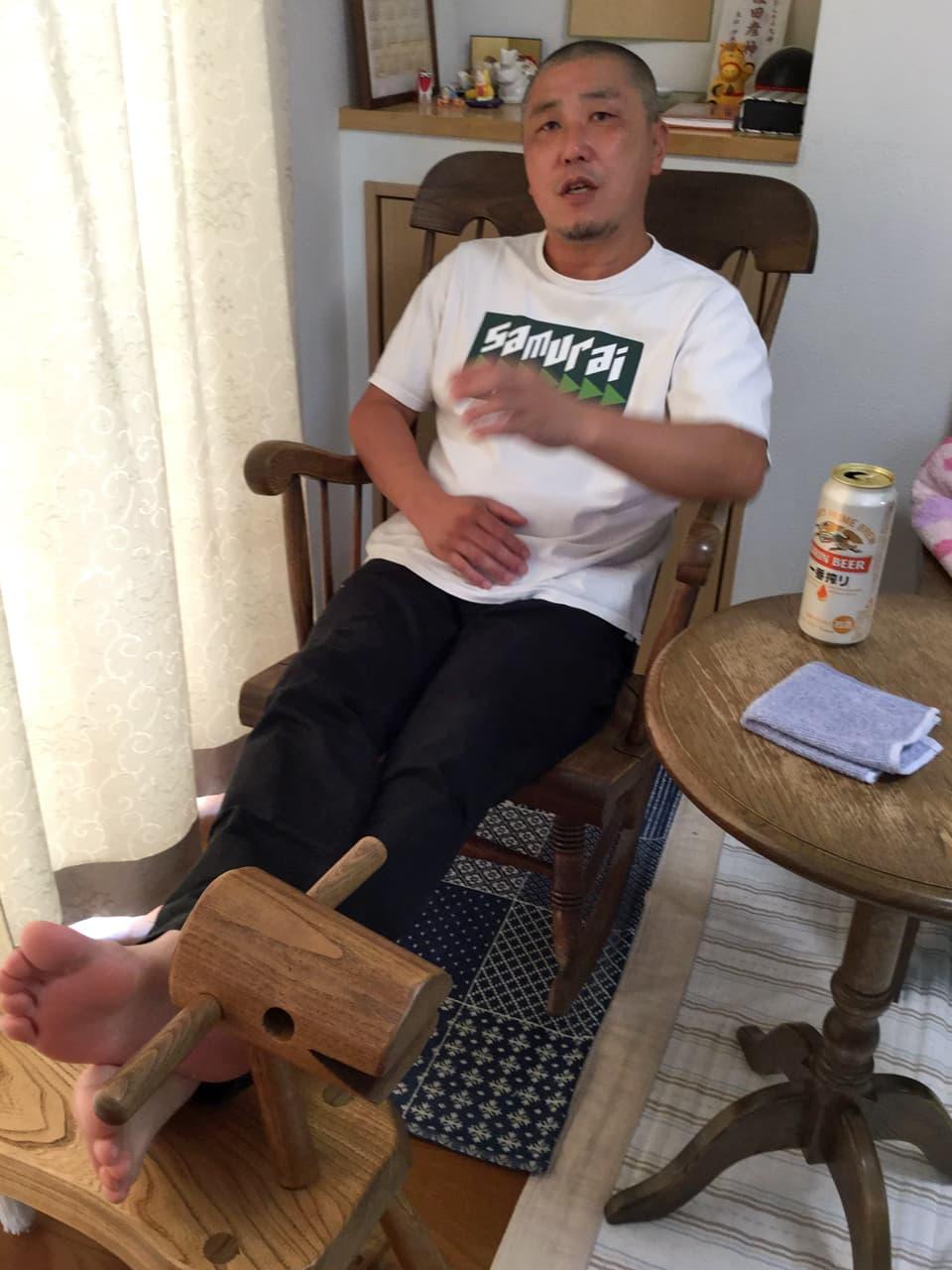 椅子に座りながらハッとした表情の竹内の様子