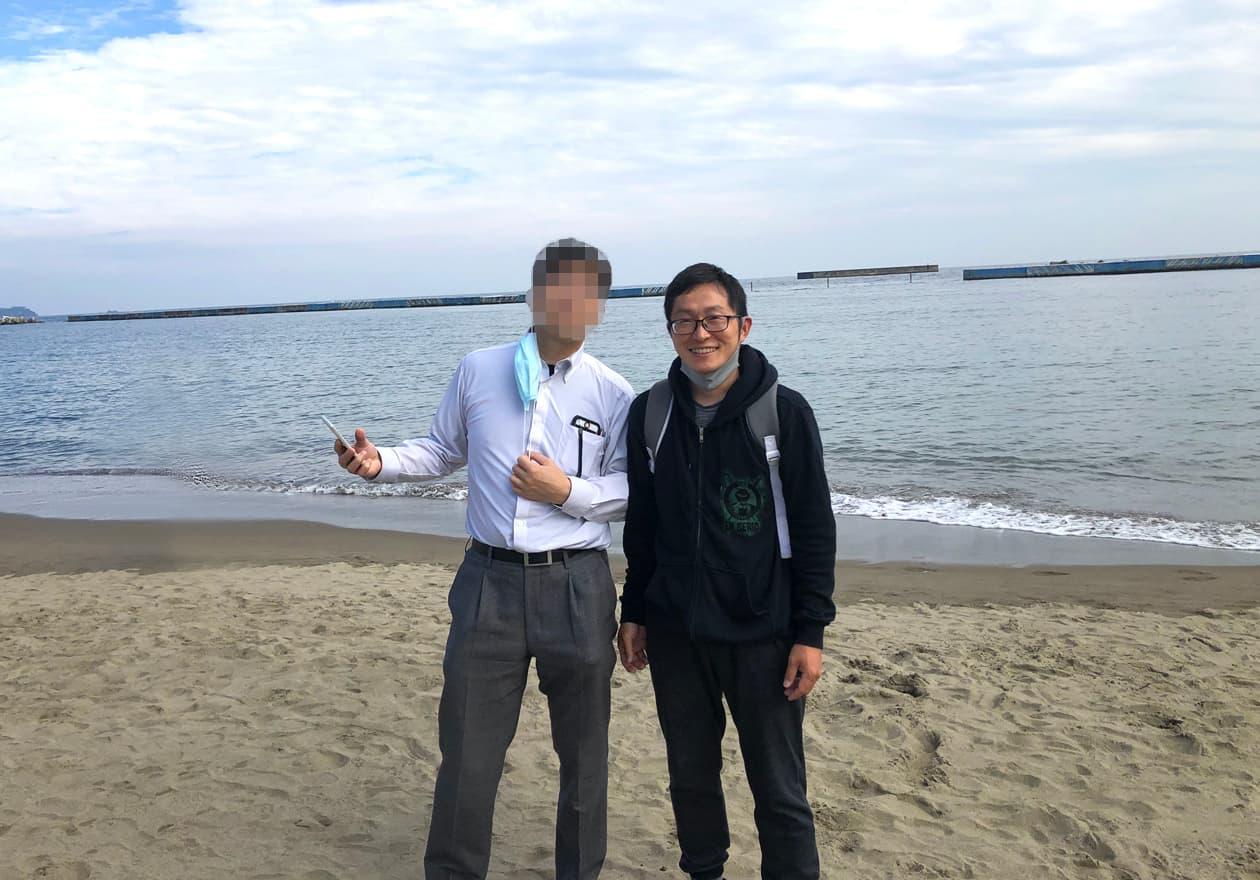 海をバックに岡本と友人が写真に写っている画像