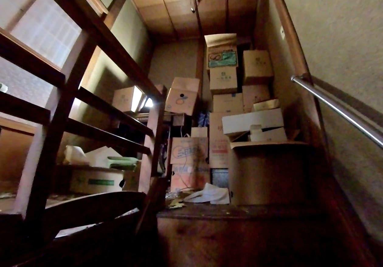 階段を上がってすぐダンボールが山積みになっている様子