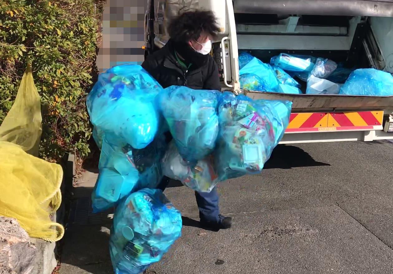 できるだけたくさんのプラスチック製容器包装を持つスタッフの様子